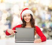 Smiling woman in santa helper hat with laptop — Stock Photo