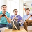 Smiling friends playing video games at home — Stock Photo #53851879