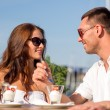 Smiling couple eating dessert at cafe — Stock Photo #53853037