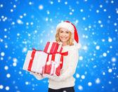 Souriante jeune femme en bonnet d'assistance avec des cadeaux — Photo