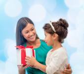 Happy mother and child girl with gift box — Stock Photo