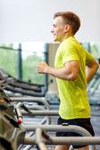 Homme souriant, exercice sur tapis roulant en salle de sport — Photo