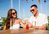 用香槟和礼品在咖啡馆新人面带笑容 — 图库照片