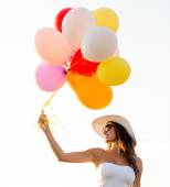 Smiling young woman in sunglasses with balloons — Foto de Stock