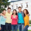 Group of smiling teenagers over campus background — Stock Photo #53994889