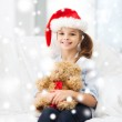 Smiling girl in santa helper hat with teddy bear — Stock Photo #53999367