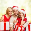 Smiling family holding gift boxes and sparkles — Stock Photo #53999401
