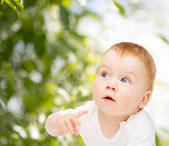 Curious baby lying on floor and looking side — Stock Photo