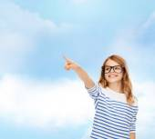 Cute little girl in eyeglasses pointing in the air — Stock Photo