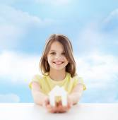Beautiful little girl holding paper house cutout — Stockfoto