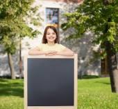 Happy little girl with blank blackboard — Stock Photo