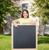 Happy little girl pointing finger to blackboard — Stock fotografie