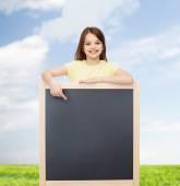 Happy little girl pointing finger to blackboard — 图库照片