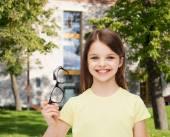 Smiling cute little girl holding black eyeglasses — Stock Photo
