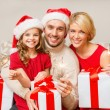 Smiling family holding gift boxes and sparkles — Stock Photo #54000205
