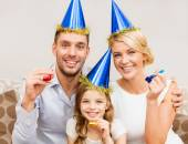 Smiling family in blue hats blowing favor horns — Stock Photo