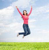 Usměvavá mladá žena skákat do vzduchu — Stock fotografie