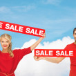 Smiling man and woman with red sale signs — Stock Photo #54149663