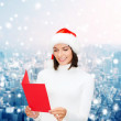 Smiling woman in santa hat with greeting card — Stock Photo #54150485