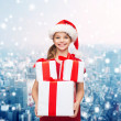 Smiling little girl in santa helper hat with gifts — Stock Photo #54151771