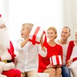 Smiling family with santa claus and gifts at home — Stock Photo #54153623