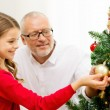 Smiling family decorating christmas tree at home — Stock Photo #54153981