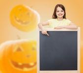 Smiling little girl with blackboard — Stock Photo