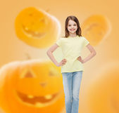 Smiling girl over pumpkins background — Stock Photo
