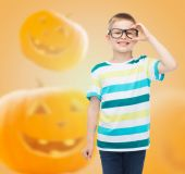 Smiling boy in glasses over pumpkins background — Stock Photo