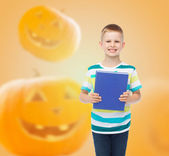 Smiling little student boy with blue book — Stock Photo