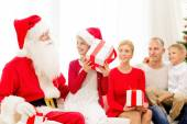 Smiling family with santa claus and gifts at home — Stock Photo