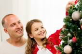 Smiling family decorating christmas tree at home — Stock Photo