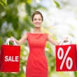 Young woman in red dress with shopping bags — Stock Photo #54316059