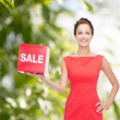 Smiling young woman in dress with red sale sign — Stok fotoğraf #54316155