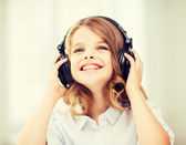 Smiling little girl with headphones at home — Photo