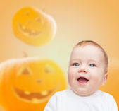 Smiling baby over pumpkins background — Stock Photo