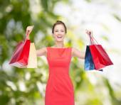 Laughing elegant woman in dress with shopping bags — ストック写真