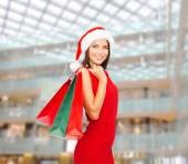 Woman in red dress with shopping bags — Stock Photo