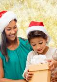 Happy mother and girl in santa hats with gift box — Stock Photo