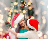 Happy mother and girl in santa hats — Stock Photo
