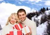 Uśmiechnięty mężczyzna i kobieta z prezentuje — Zdjęcie stockowe