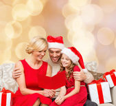 Happy family in santa helper hats with gift boxes — Stock Photo