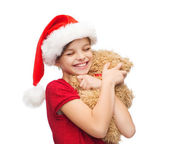 Smiling girl in santa helper hat with teddy bear — Stock Photo