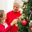 Smiling family decorating christmas tree at home — Stock Photo #54322397