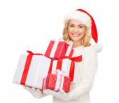 Woman in santa helper hat with many gift boxes — Stock Photo