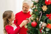 Smiling family decorating christmas tree at home — Stok fotoğraf
