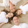 Parents and two girls lying on floor at home — Stock Photo #54402855