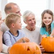 Happy family sitting with pumpkins at home — Stock Photo #54403219