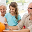 Happy family sitting with pumpkins at home — Stock Photo #54403385