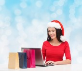 Smiling woman in santa hat with bags and laptop — Stock Photo